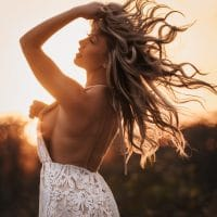 Beautiful blonde fitness woman Hannah Smith wearing a transparent white dress in a sunset photoshoot with her arm up showing side boob and bare back