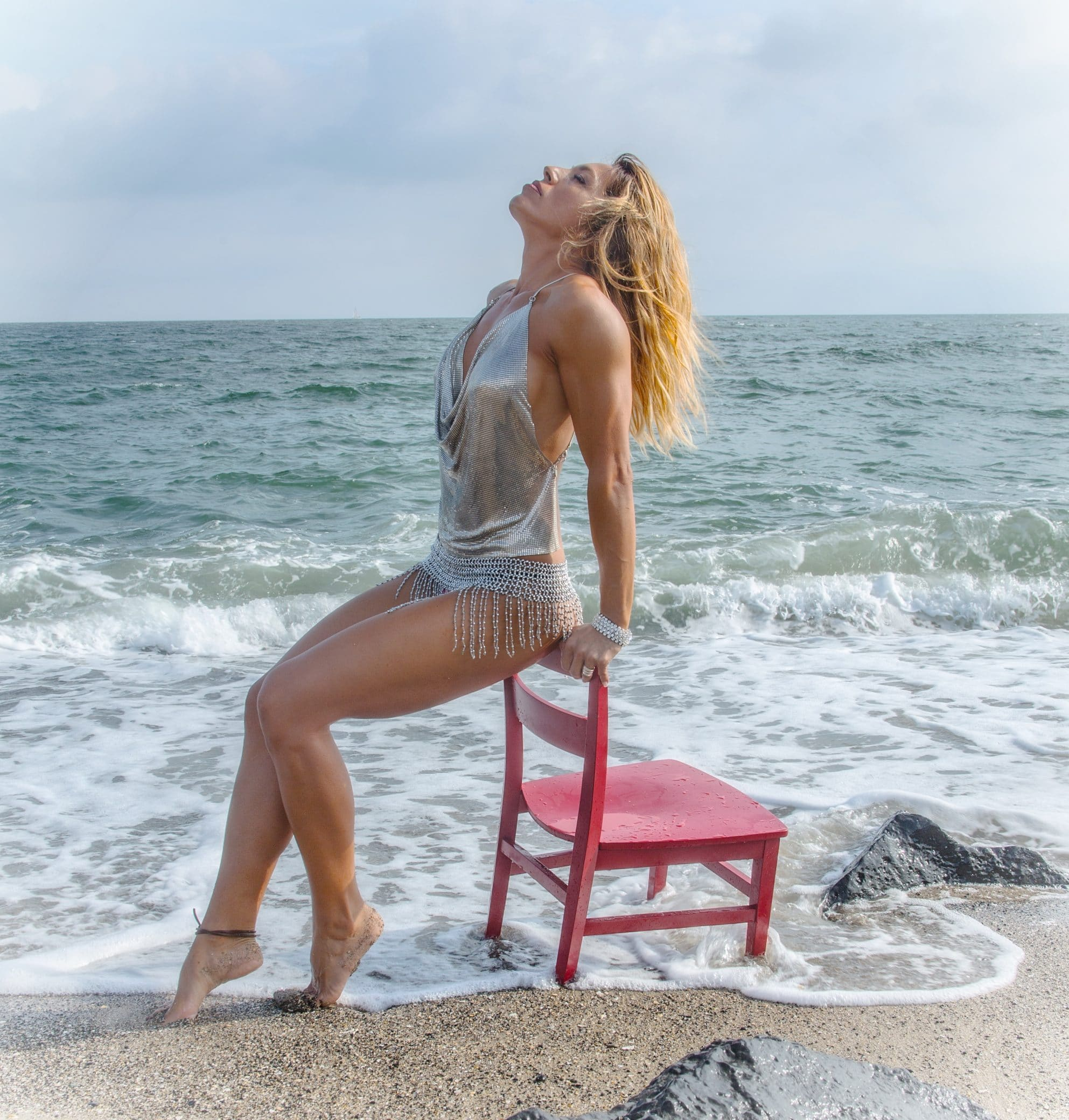 Beautiful blonde model on the beach wearing a silver camisole and a fringed pearls skirt sitting on a red wooden chait showing her long sexy legs and feet