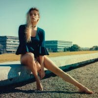 Beautiful blonde woman Camila Sol Botti wearing a green long sleeves blouse sitting on concrete for an outdoor photoshoot giving a sexy look displaying her long sexy bare legs