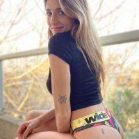 Beautiful argentian woman model Camila Sol Botti smiling with tattoos wearing a black crop top and a bikini bottom sitting by the window showung her bare thigh and part of her ass