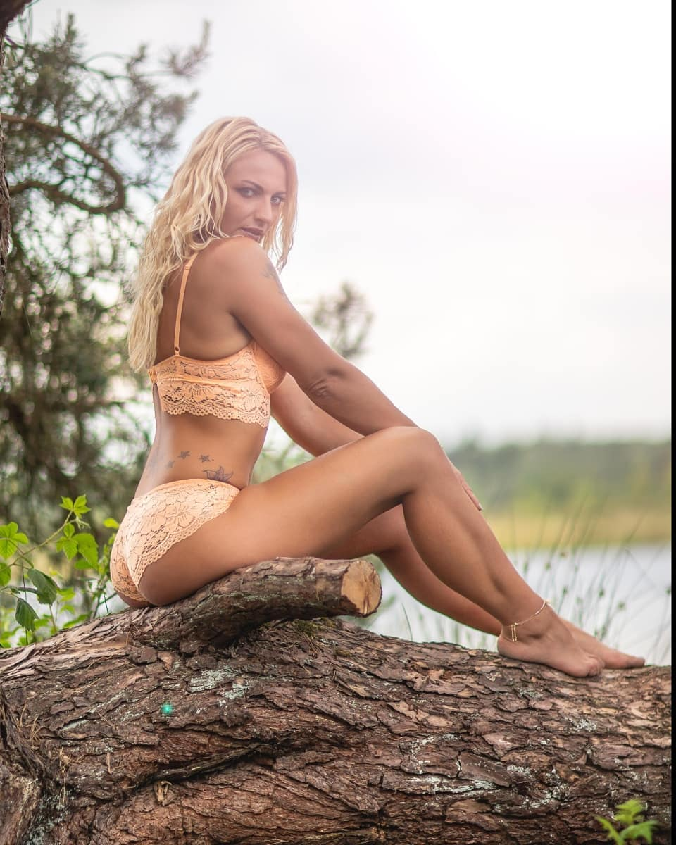 Beautiful tattooed Dutch model Willeke Bartels wearing peach lingerie sitting on a log in front of a lake looking over her shoulder showing her sexy ass, toned legs and bare feet