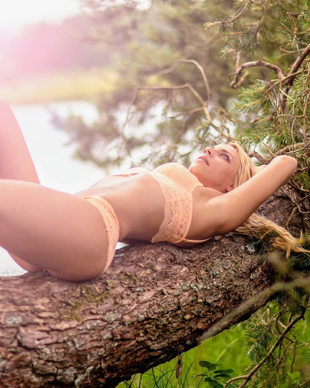 Beautiful tattooed Dutch fitness model and mom Willeke Bartels wearing peach lace lingerie lying on a log looking up with her arms up showing her toned abs and under arms