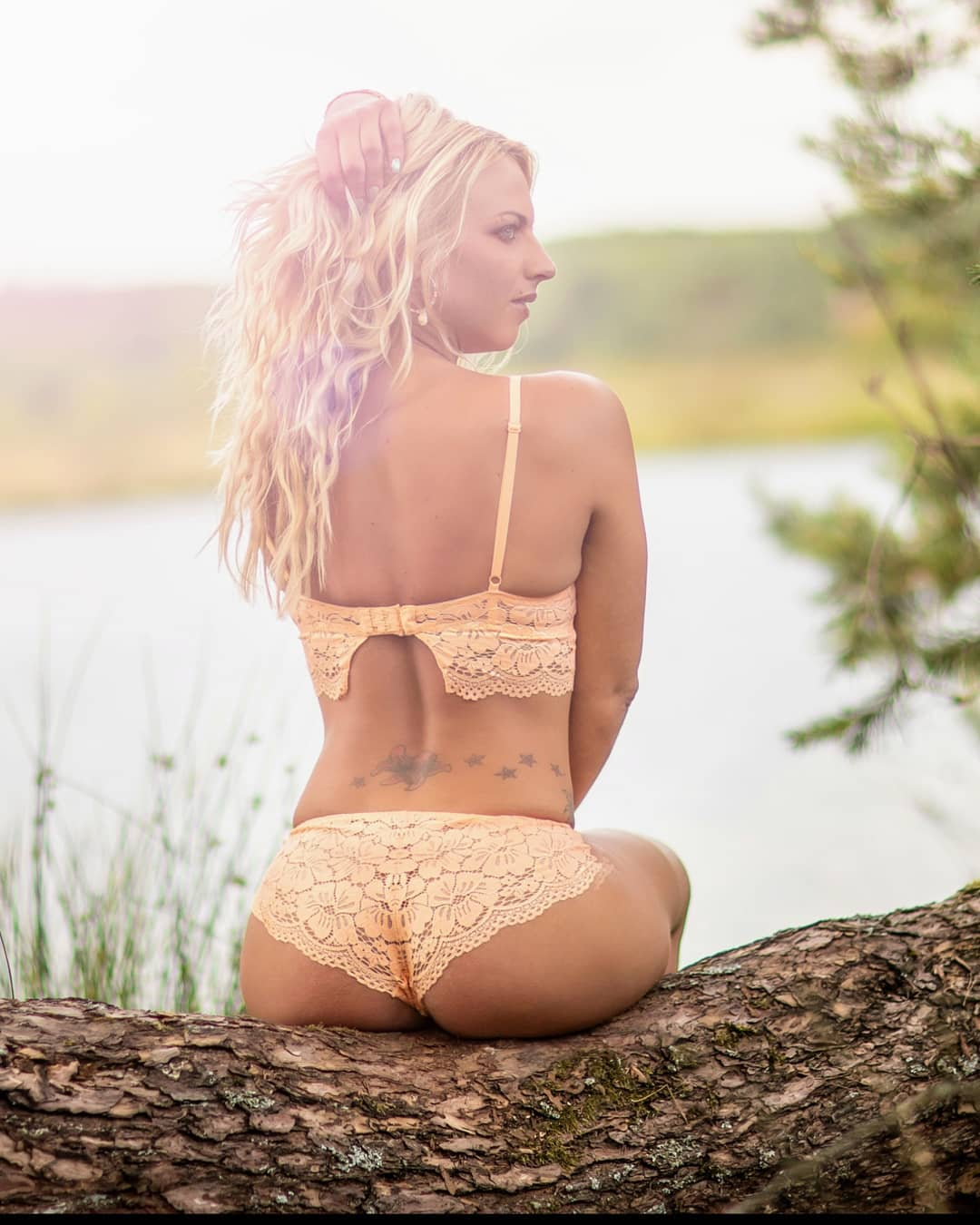 Beautiful Dutch model Willeke Bartels wearing peach lingerie sitting on a log looking over her shoulder showing her sexy tattooed bare back