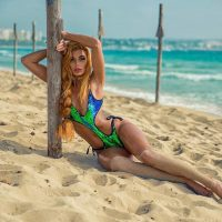 Beautiful natural redhair model wearing colourful swimwear for a summer photo shoot at the beach