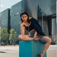 Beautiful asian Canadian model Hylie M. L. wearing a black top and high heels sitting outside on a cube with her sexy legs crossed pointing her chin for a city photoshoot. Photo by Kelvin Vinx Comendador @vinxreddervon