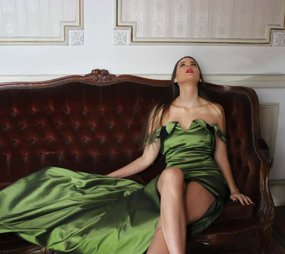 Beautiful model and actress MaLa Rodriguez wearing a classy Dalvi Rivero green dress and black high heels shoes sitting on a sofa with her bare legs crossed