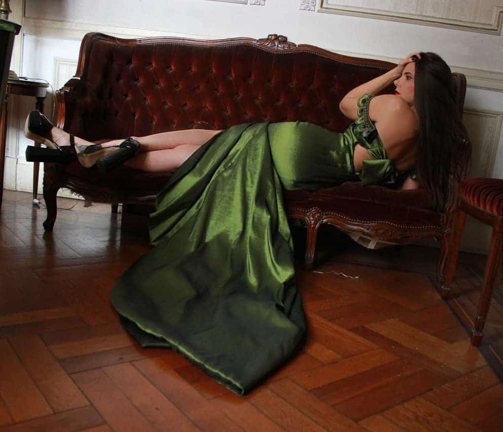 Beautiful model and actress MaLa Rodriguez wearing a classy Dalvi Rivero green dress and black high heels shoes lying on a victorian sofa showing her bare back and calves
