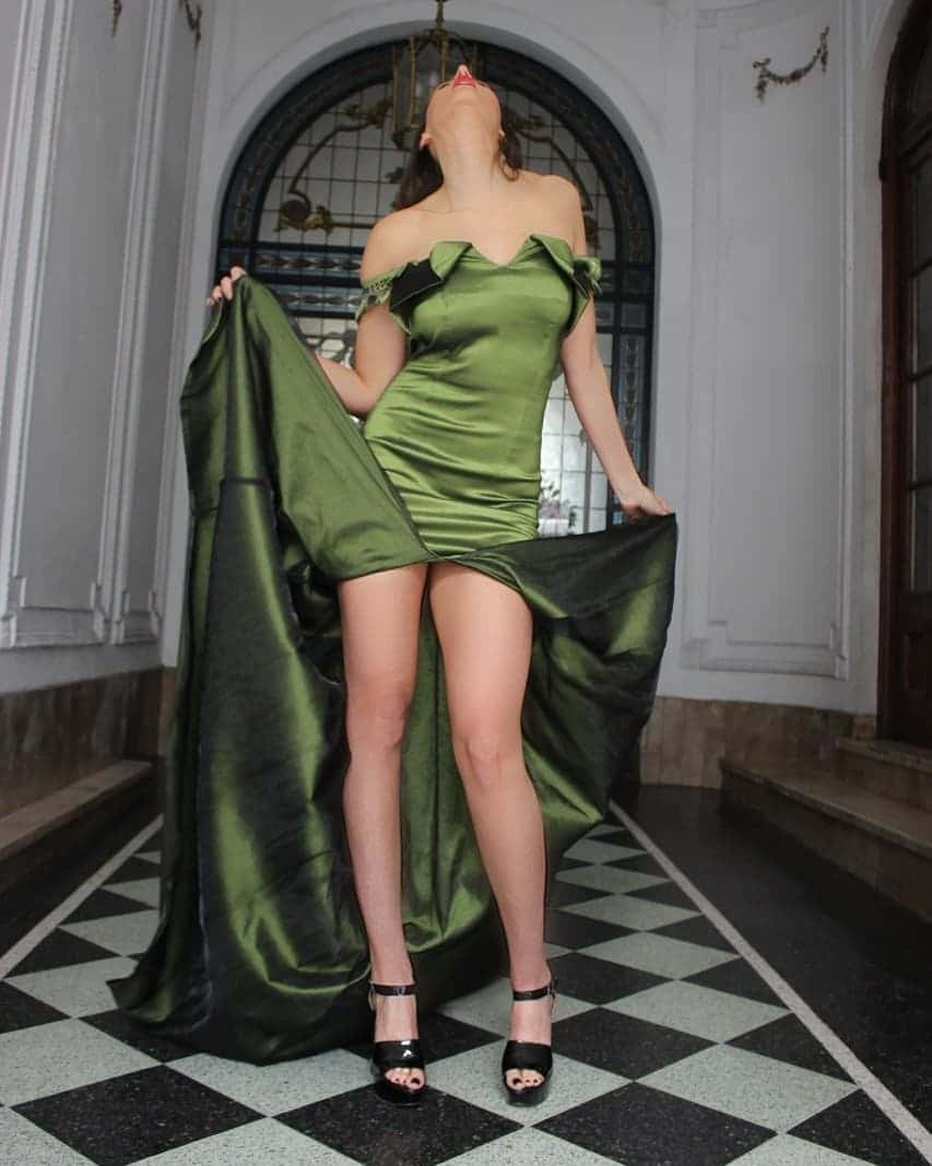 Beautiful model and actress MaLa Rodriguez wearing a classy Dalvi Rivero green dress and black high heels shoes standing lifting her dress up showing her long sexy legs and feet with black toe nail polish
