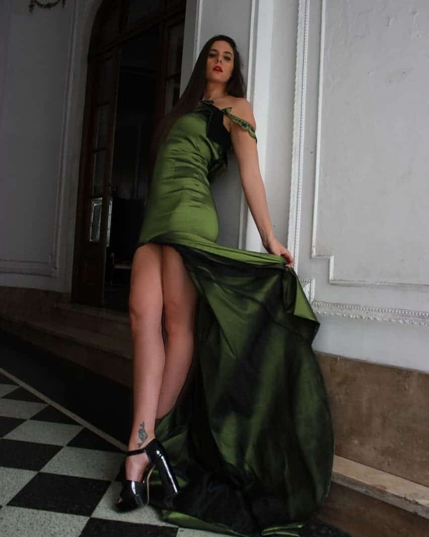 Beautiful model and actress MaLa Rodriguez wearing a classy Dalvi Rivero green dress and black high heels shoes leaning on a wall opening her dress to show her bare tattooed legs and feet