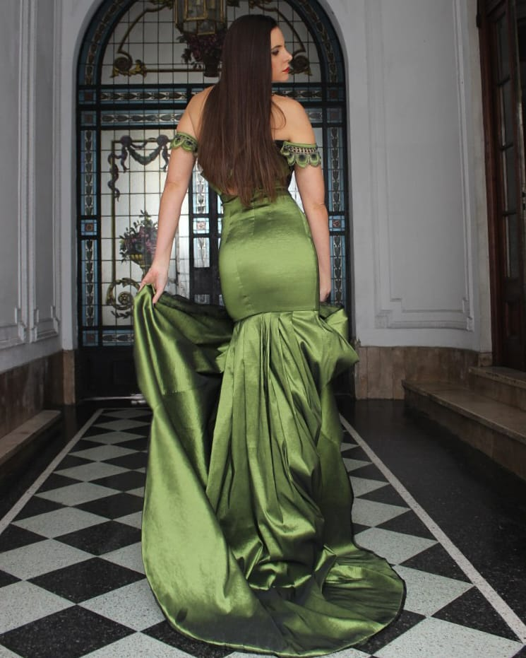 Beautiful model and actress MaLa Rodriguez wearing a classy Dalvi Rivero green dress and black high heels shoes standing in the hallway looking above her shoulder