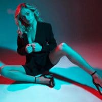 Beautiful blonde model wearing a black jacket, black shorts and black high heels for a red and blue photoshoot