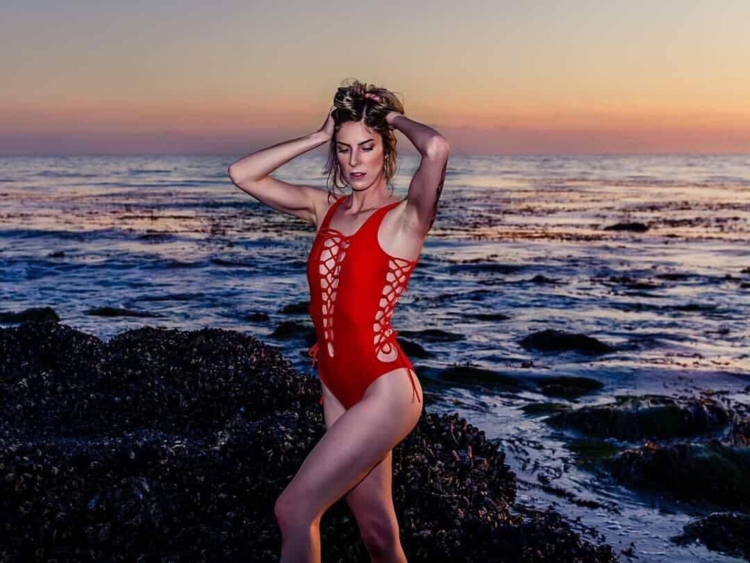 Beautiful model Cherish at the beach wearing a red swimwear modelling with her arms up holding her blond hair