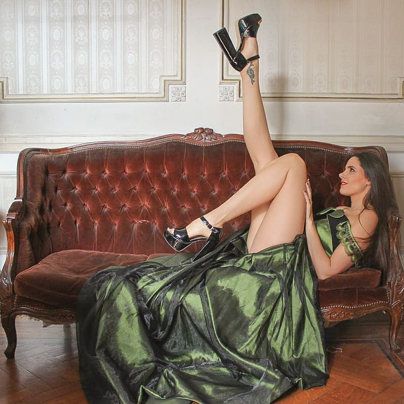 Beautiful model and actress MaLa Rodriguez wearing a classy Dalvi Rivero green dress and black high heels shoes sitting on a vintage sofa with her sexy legs up smiling