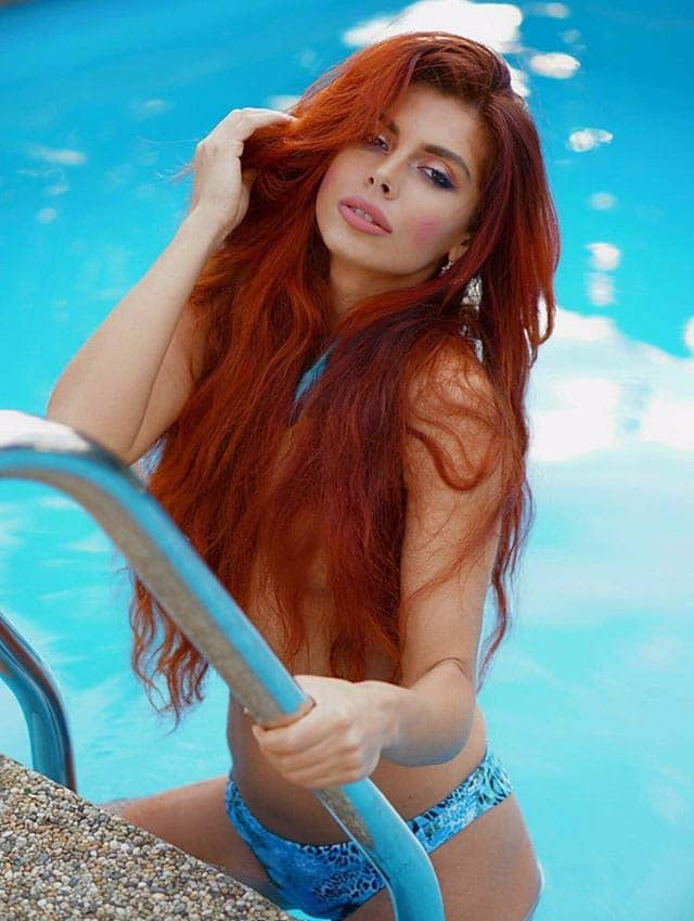 Beautiful redhead czech model Slavena Albastova wearing a blue bikini getting out of a pool giving a sexy look