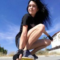 Beautiful young woman skateboarding in the street wearing a black t-shirt and denim shorts