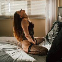 Beautiful young model Kat Toaster wearing black and red lingerie and fishnets kneeling on a bed with her hands between her thighs for a sexy photo. Photo by Kelvin Vinx Comendador