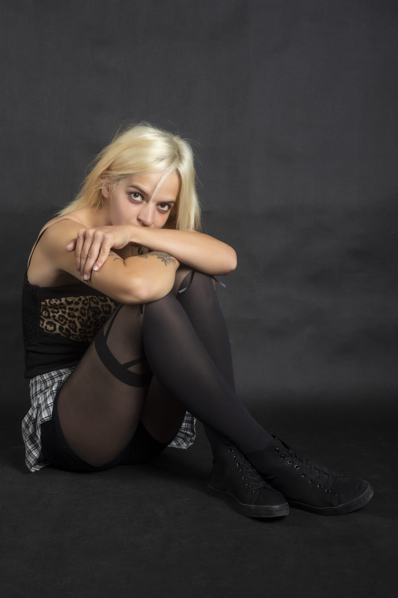 Beautiful blonde woman sitting on the floor resting her