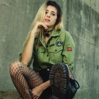 Beautiful blonde model Camila Sol Botti wearing a green shirt, fishnets nylons and black boots sitting on concrete looking back at the camera