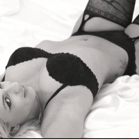 Beautiful Dutch model wearing black lingerie lying in bed for a black and white photoshoot