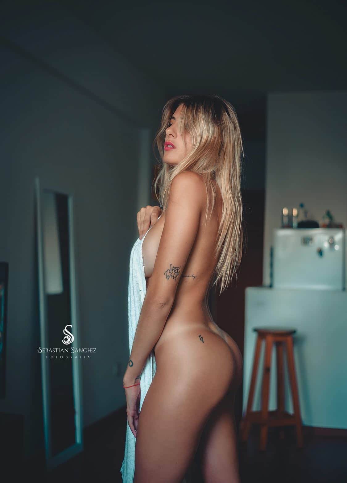 Beautiful blonde Argentine tattooed model Camila Sol Botti in the nude for a boudoir photoshoot showing her bare ass cheeks