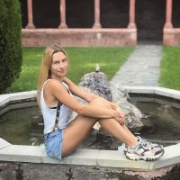 Beautiful tattooed Spanish model Sareta MJ wearing a white camisole and denim shorts sitting on a water fountain showing her long sexy legs