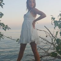 Beautiful Canadian model McKenzie Lubeck wearing a light white summer dress showing hes sexy legs with her hands on her waist in a behind the scene photography at Lake Huron