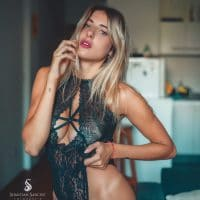 Beautiful blonde Argentine tattooed model wearing black lingerie in a boudoir photoshoot