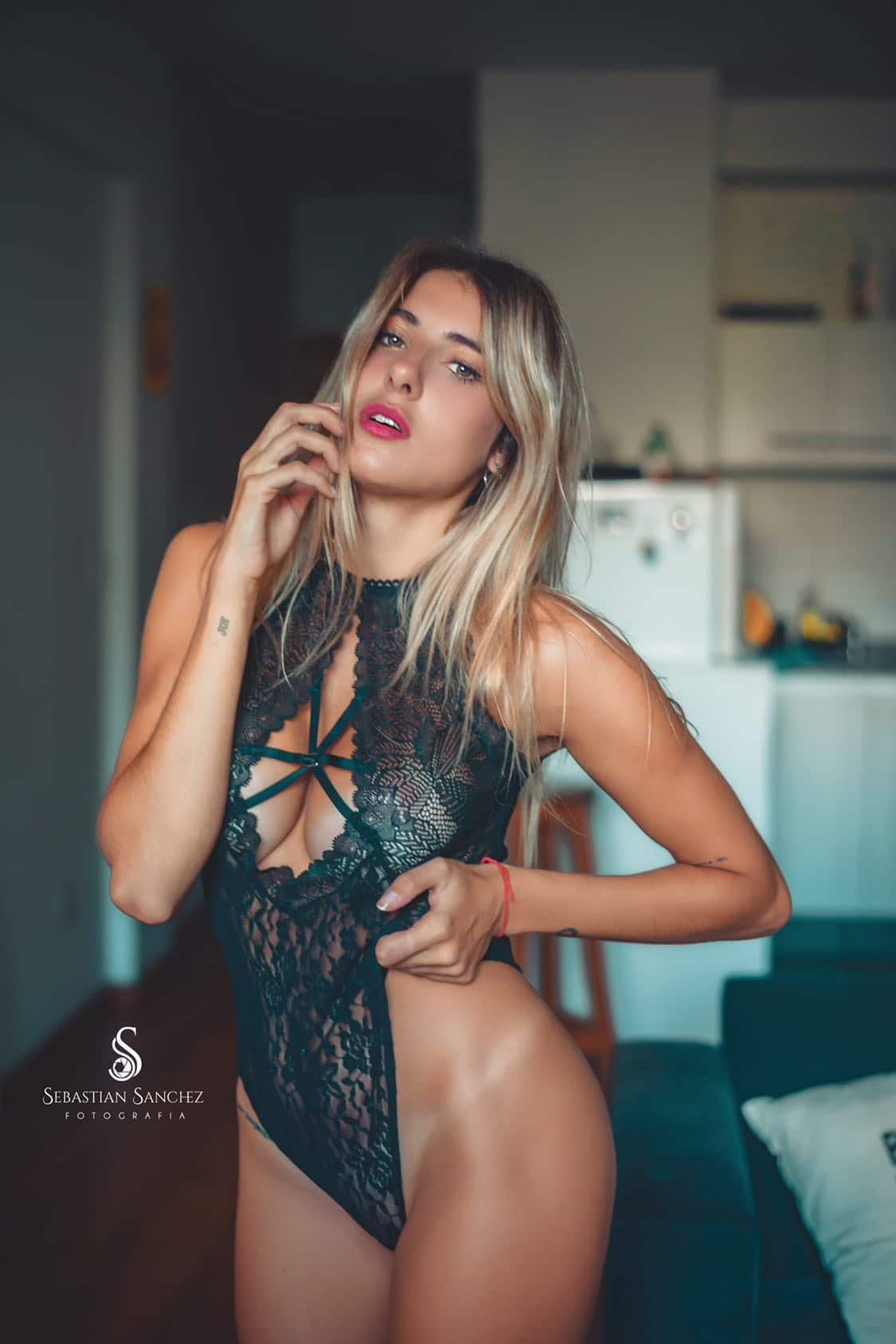 Beautiful blonde Argentine model Camila Sol Botti wearing transparent black lace lingerie for a boudoir photoshoot showing cleavage with her mouth open