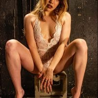 Beautiful blonde model and mom Kaitlin wearing white lace lingerie sitting on a concrete block bare feet with her legs opened hiding her crotch with her hands looking bask at the camera