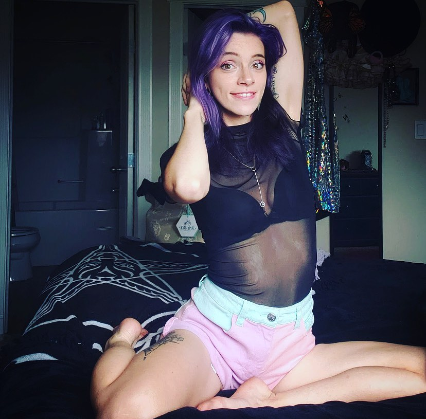 Beautiful Canadian goth girl Tora Reign wearing pastel shorts with a transparent black nylon top sitting in her bed with her arms up showing her sexy legs and bare feet