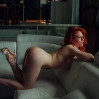 Beautiful redhead model in the nude wearing white high heels in a boudoir photoshoot
