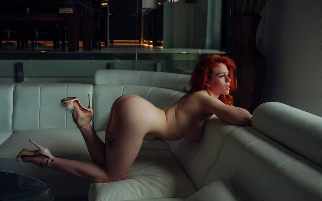 Beautiful redhead model Jolene Fox in the nude wearing white high heels in a boudoir photoshoot bending over on a leather sofa showing her sexy body and bare ass