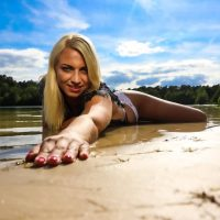Beautiful model lying in the beach sand with her hand forward smiling