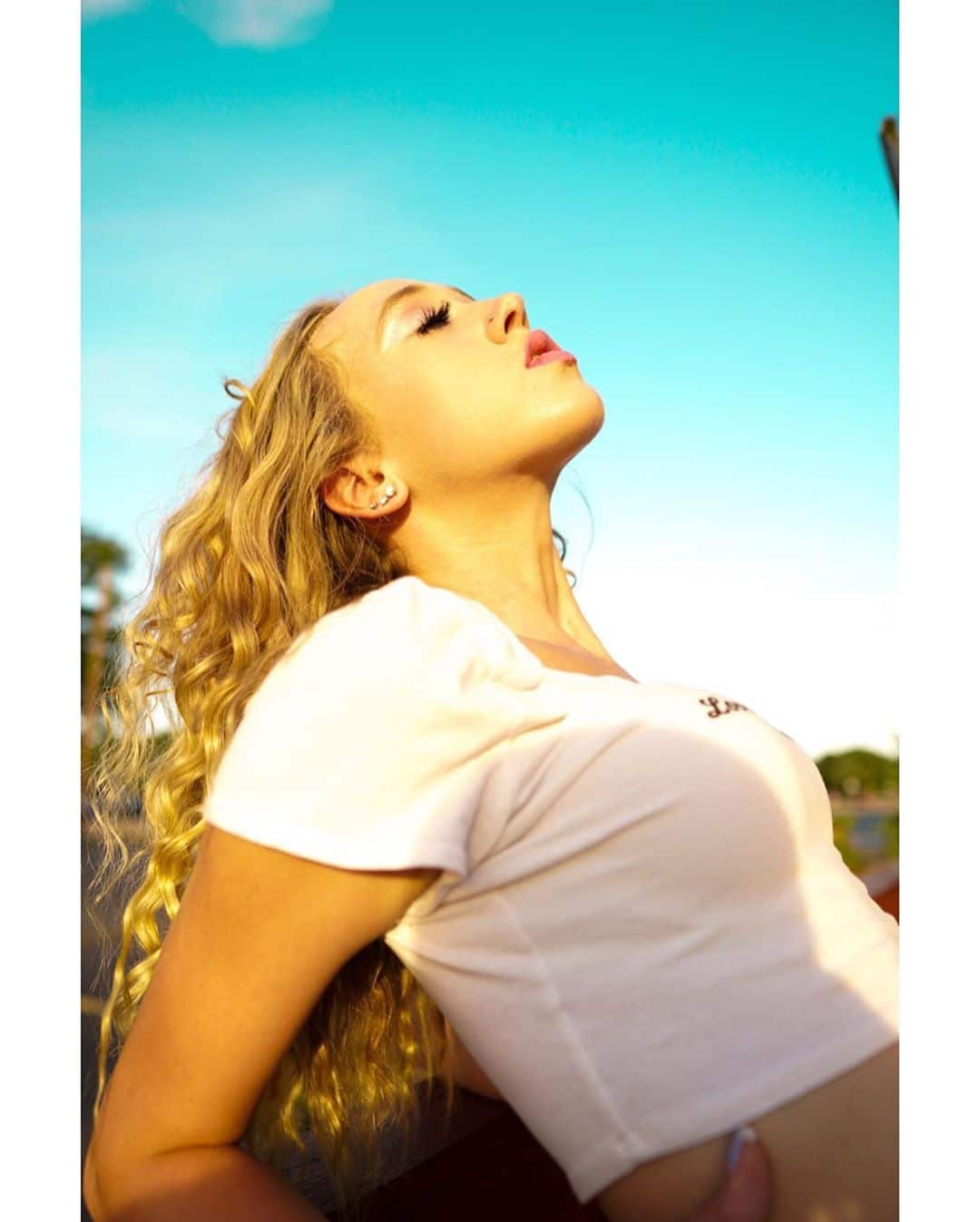 Beautiful young blonde American model Alyssa Hensley (asap.ally) wearing a crop white t-shirtsoaking up the sun on summer day