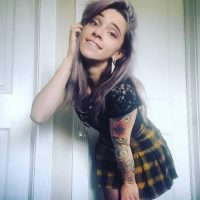 Beautiful tattooed Canadian alt model wearing a black top with yellow and black skirt and black nylons