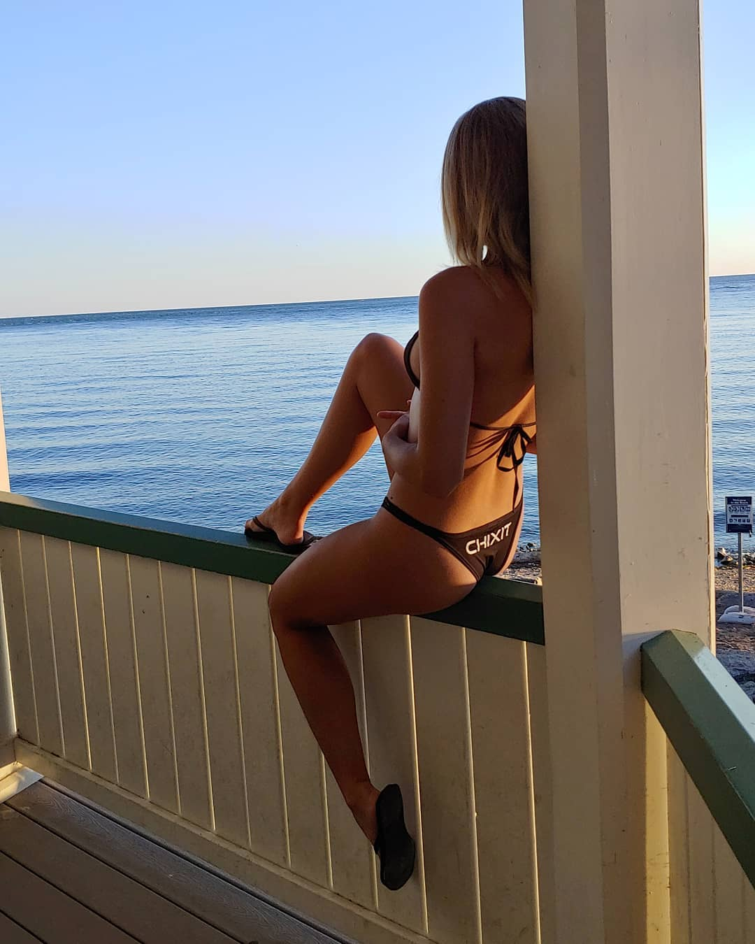 Beautiful young Canadian model McKenzie Lubeck wearing a black Chixit bikini in front of an Ontario Lake showing her sexy legs  looking at the sunset