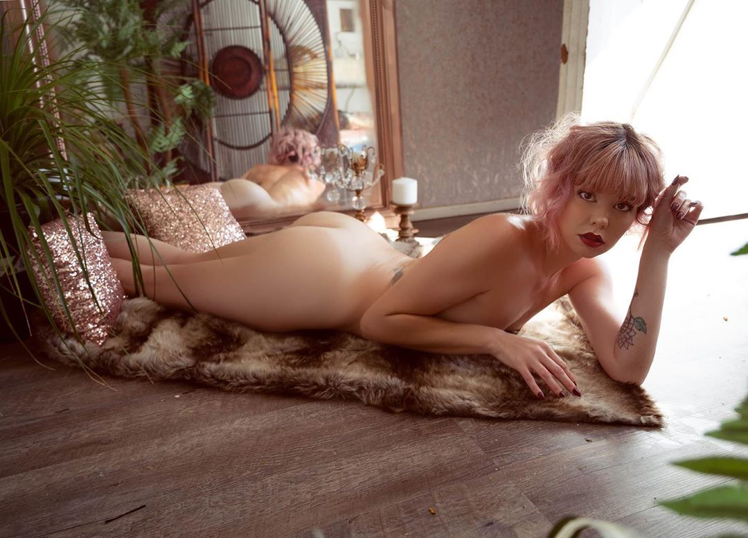 Beautiful boudoir model Gooty @gootyxo in the nude lying on a fur rug looking back at the camera showing her fit body and bare ass. Photo by Portrait&Boudoir Photography shotsfiredphotostyling