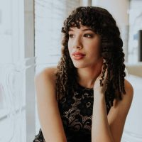 Beautiful young author, composer and singer from Quebec wearing a black lace dress sitting by the window smiling