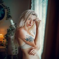 Beautiful French model wearing white lace lingerie for a boudoir photo shoot