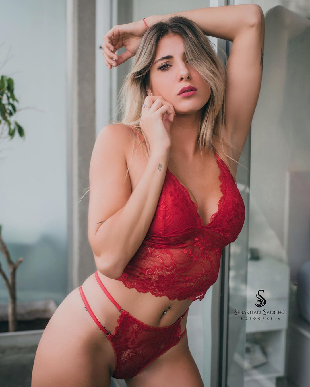 Beautiful Argentinian model Camila Sol Botti wearing red lingerie with her arm up whiwing her incredible fit body and her belly piercing