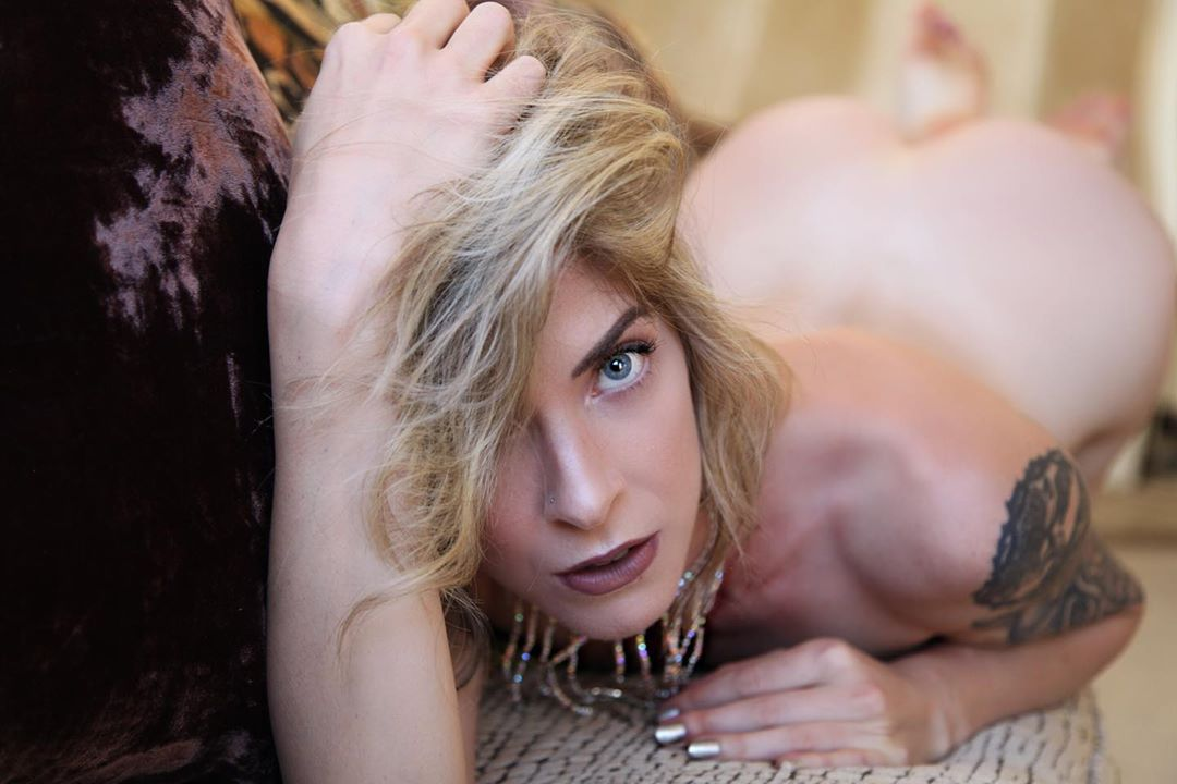 Beautiful blue eyed American blonde tattooed model Cherish lying in the nude for a boudoir close up portrait showing her bare ass in the background