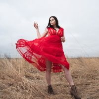 Beautiful American model Courtney Anderson wearing a transparent red dress lifted by the blowing wind showing her sexy bare legs