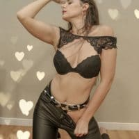 Beautiful model wearing leather pants and a black lace bra on her knees for a sexy photoshoot