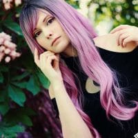 Beautiful pink haired goth cosplayer and model wearing a black witch dress in the middle of the wood