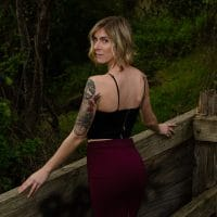 Beautiful Blue eyed Tattooed American Model Cherish wearing a black top and a short red skirt looking over her bare shoulder showing her sexy back