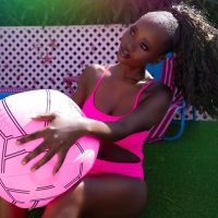 Beautiful ebony model Bijoux Rwiyaza @beautybybijoux wearing a pink bikini for a summer photoshoot by Portrait&Boudoir Photography @shotsfiredphotostyling sitting on the ground holding a ball with her hair in a pony tail