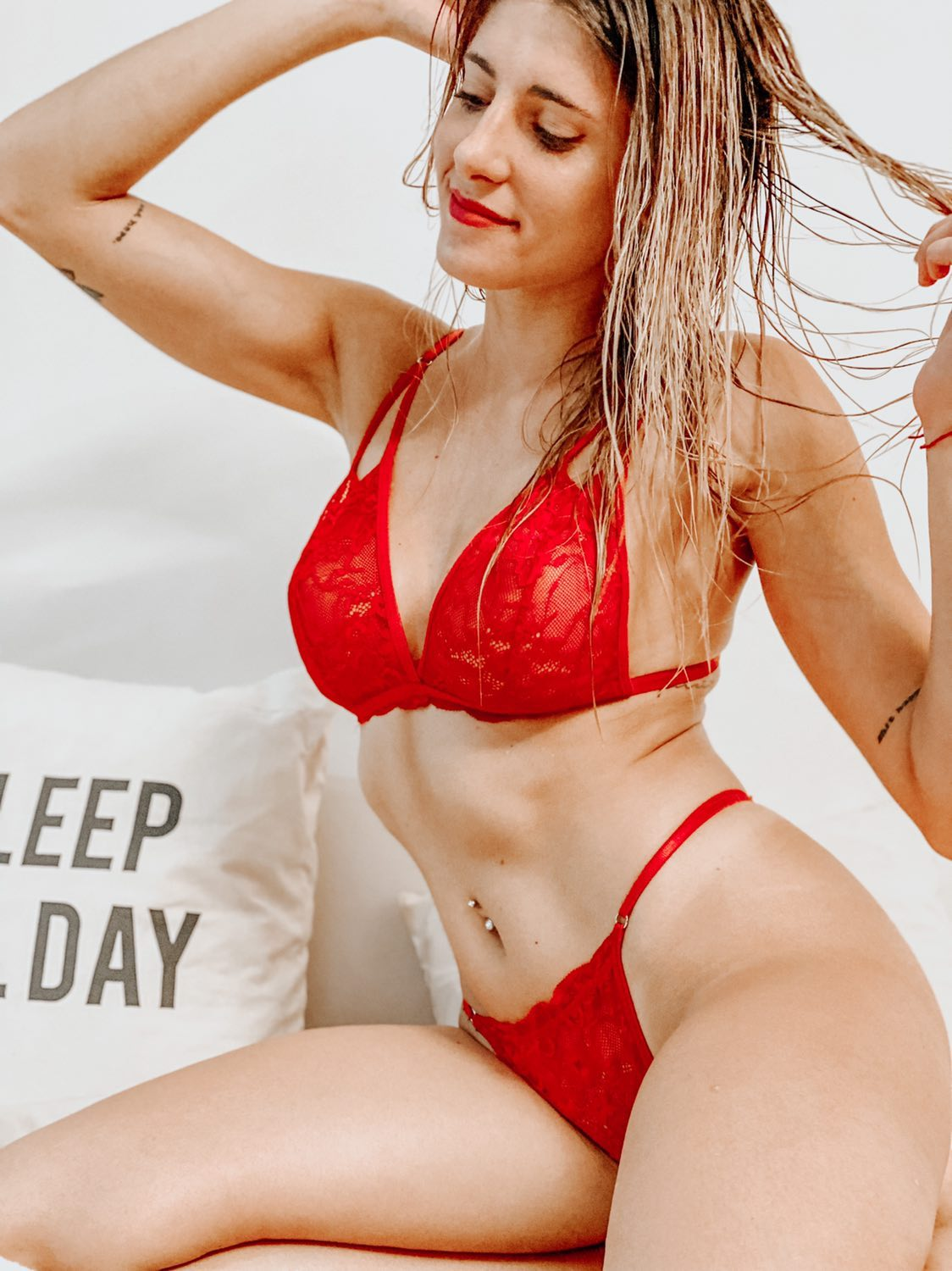 Beautiful Argentinian model Camila Sol Botti @csbotti having fun in a photo session wearing red lace lingerie sitting with her arms up smiling showing her hot latina body