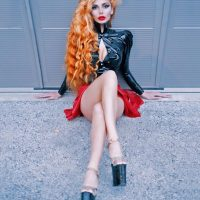 Beautiful Czech model Slavena Albastova @naturalredheadtiger wearing a red short skirt and a latex black top sitting on the ground with her long sexy legs crossed showing massive cleavage