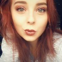 Beautiful Canadian redhead woman Shyanne Brook in a close up selfie blowing a kiss with her red lips