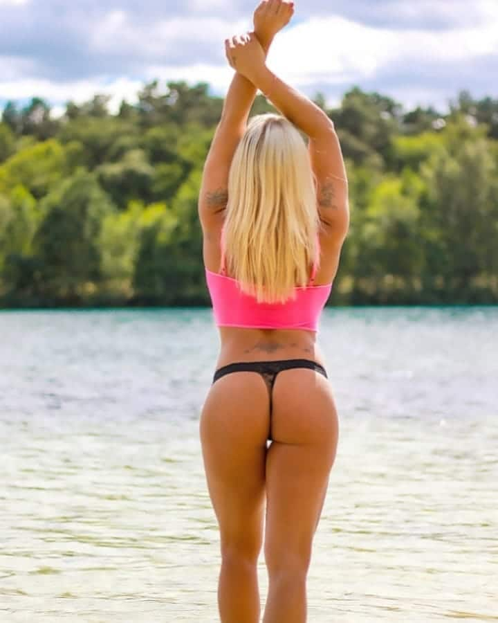 Beautiful blonde Dutch fitness model and mom Willeke Bartels @willekebartels.fitmodel at the beach shot from behind showing her sexy round ass holding her arms up